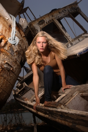 portrait of sexy blond woman in jeans posing in from of shipwreck photo