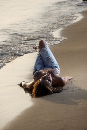 Beautiful young sexy fashion model in jeans by the sea at sunrise photo