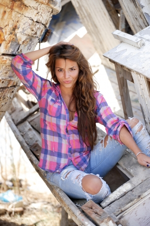portrait of sexy brunette woman posing in from of shipwreck photo