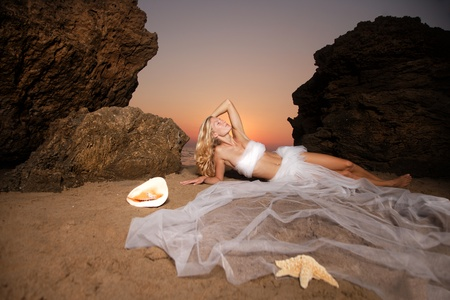 Beautiful young woman on the beach wrapped in white wedding veil at sunrise photo