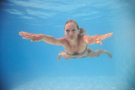 Frau Schwimmen unter Wasser im Schwimmbad