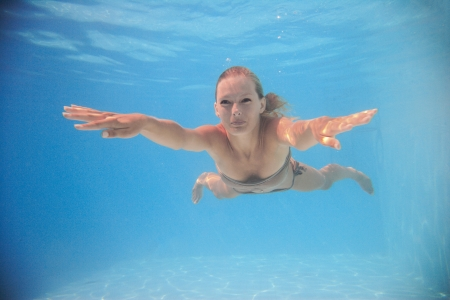 Woman swimming  underwater in swimming pool photo