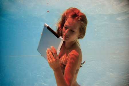 Woman using a tablet PC underwater in swimming pool Stock Photo - 15106180