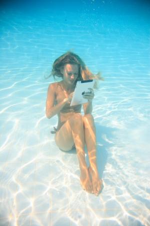 Frau mit einem Tablet-PC unter Wasser im Schwimmbad