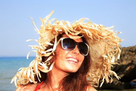 Girl on a tropical beach with hat and sunglasses photo