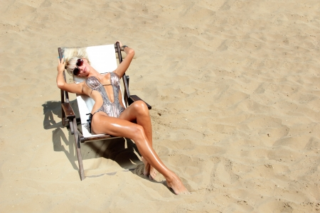 Young beautiful blond woman on sunbed on the beach photo