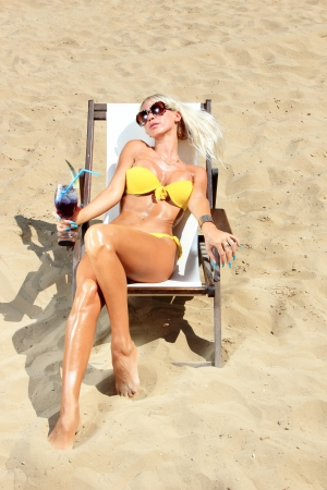 Young beautiful blond woman tanning on sunbed on the beach Stock Photo - 16506706