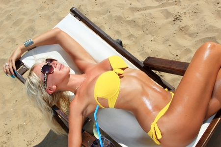 Young beautiful blond woman tanning on sunbed on the beach photo
