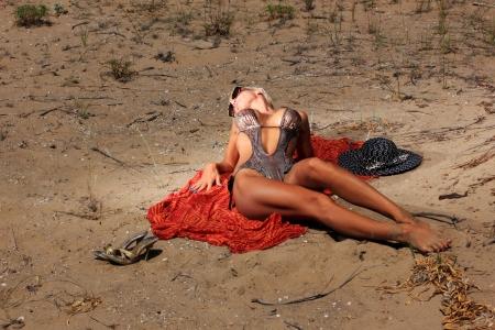 The beautiful bikini model posing  on the sandy beach Stock Photo - 16507781