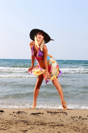 Young woman in dress and straw hat walking on beach photo