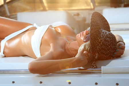 Young and sexy woman in white laying on luxurious yacht