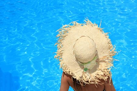 Young woman with hat enjoying a swimming pool Stock Photo - 16488112