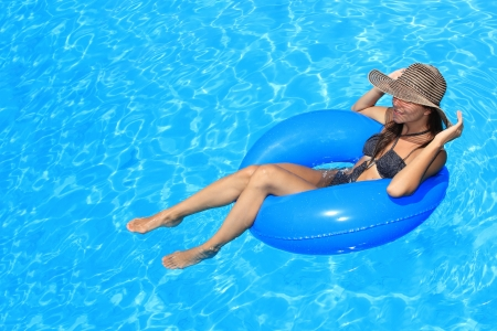 Young woman with hat enjoying a swimming pool Stock Photo