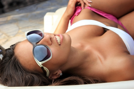 Pretty female with sunglasses on at the beach photo