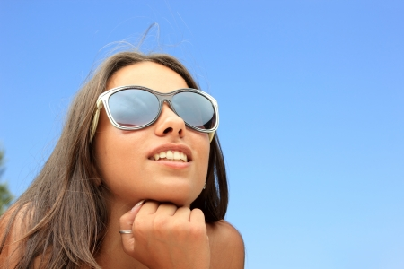 Pretty female with sunglasses on at the beach