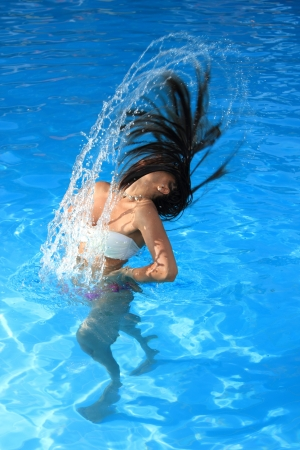 A beautiful woman relaxing in the pool with water splash photo