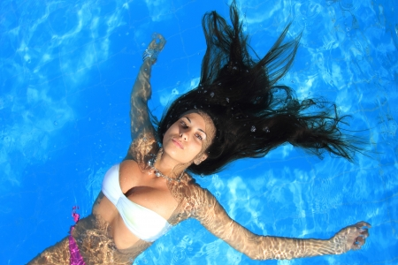 A beautiful woman relaxing in the pool photo