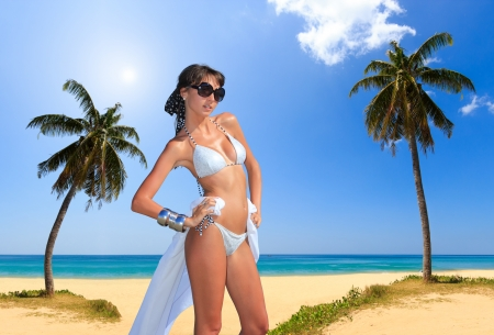 Beautiful woman on a tropical  beach with palm trees on background photo