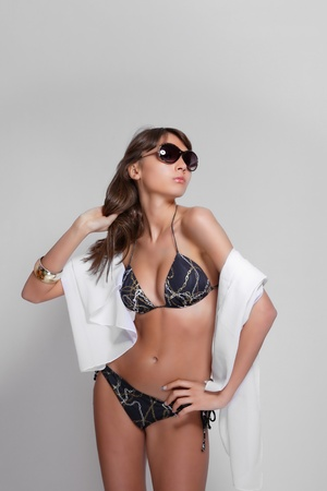 tanned woman wearing a bikini with sunglasses   photo