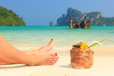 caribbean drink: Coconut cocktail with drinking straw and womans legs on the beach Stock Photo