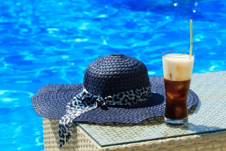 fredo: Fredo Caffè di ghiaccio contro chiaro blu acqua della piscina con cappello di paglia