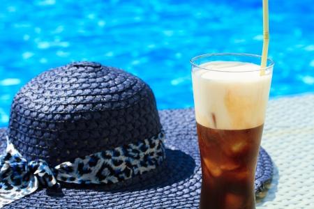 fredo: Ice Fredo caffè contro acqua blu chiaro della piscina con il cappello di paglia