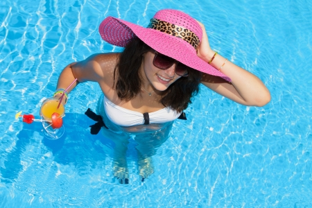 Young woman in the swimming pool holding a cocktail glass photo
