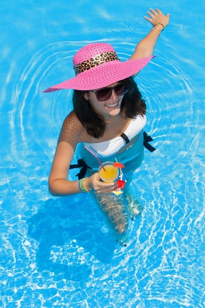 Pretty brunette woman in a hat enjoying cocktail in a swimming pool photo