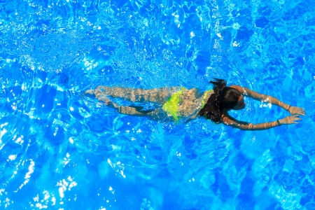 diving pool: woman with swimsuit swimming on a blue water pool