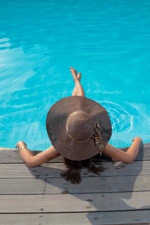 Junge Frau im Bikini mit Strohhut sitzt im Schwimmbad