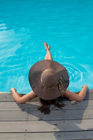 Young woman in bikini wearing a straw hat sitting in the swimming pool