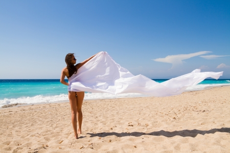 pareo: Beautiful Girl With White sarong on The Beach. Travel and Vacation. Freedom Concept