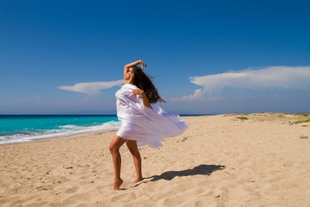 Beautiful Girl With White fabric on The Beach. Travel and Vacation. Freedom Concept. photo