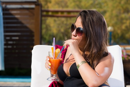 Young woman relaxing by the swimming pool enjoying her fresh cocktail photo