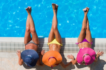 Three women in bikini wearing a straw hat by the swimming pool Stock Photo