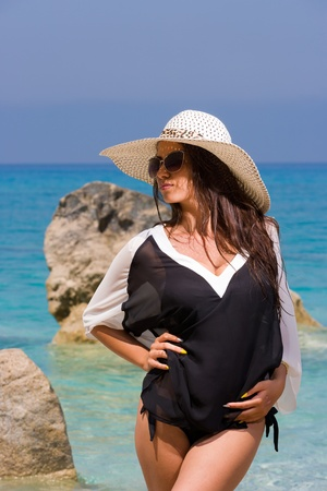 Summer vacation woman on the beach in beach hat enjoying summer holidays looking at the ocean photo