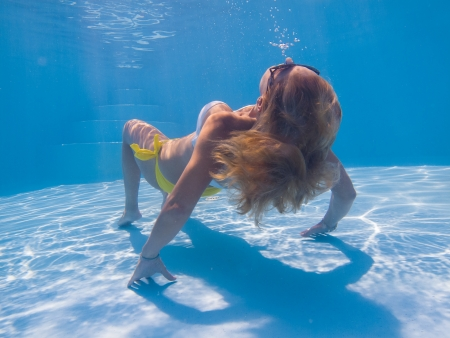 Young woman undewater in the swimming pool photo