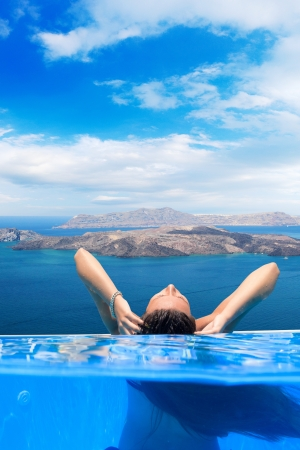 Over Underwater Young woman enjoying the view of Santorini island Greece photo