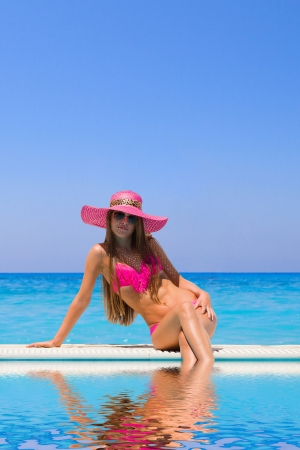 Young woman in bikini wearing a straw hat by the swimming pool photo
