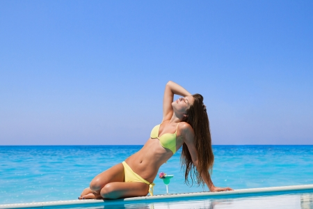 Young woman in bikini  by the swimming pool photo