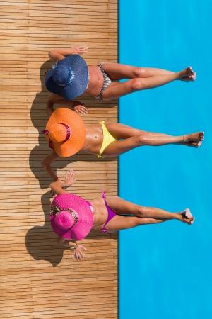 Drei Frauen reaxing auf dem Deck am Pool an exotischen Ferienort