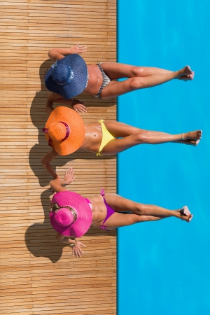 Three women reaxing on the deck by the swimming pool at exotic resort