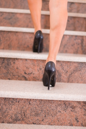 Businesswoman taking step to higher level on stairway Imagens