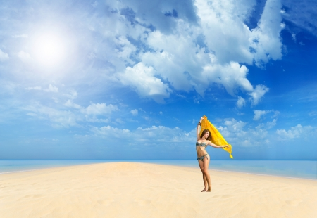 Beautiful Girl With yellow sarong on The Beach. Travel and Vacation. Freedom Concept. photo