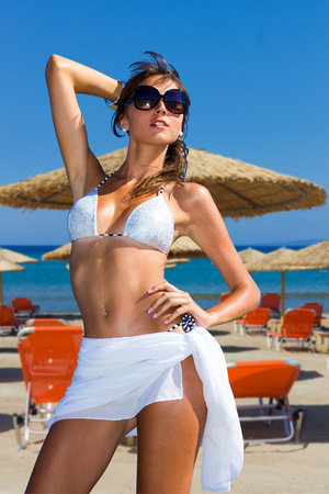Beautiful young woman in bikini with sunglasses on the beach photo