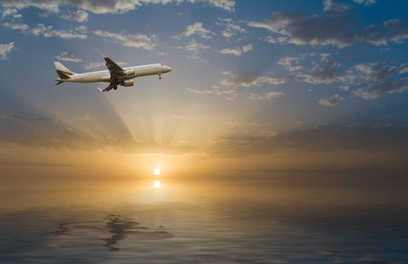 commercial jet airplane in flight at sunset above the sea photo