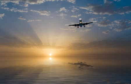 approaching: commercial jet airplane in flight at sunset above the sea Stock Photo