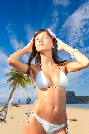 Young woman relaxing on the beach at exotic resort photo