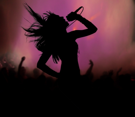 singer with microphone: Female singer silhouette at rock concert
