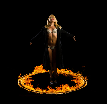 Woman in a circle of fire Blazing flames over black background photo